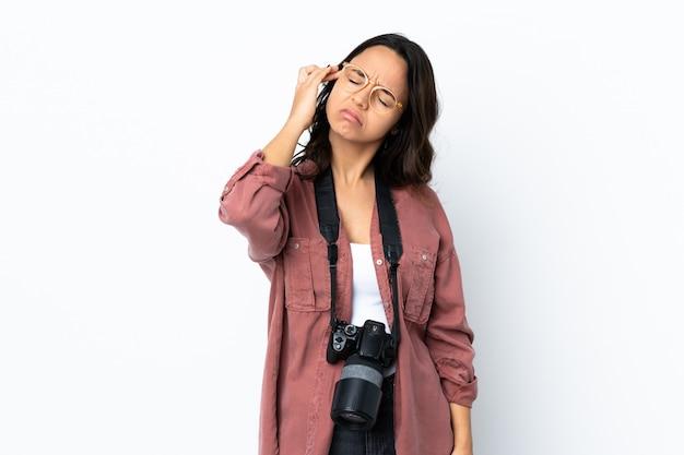 Junge fotograffrau über weißer wand mit kopfschmerzen
