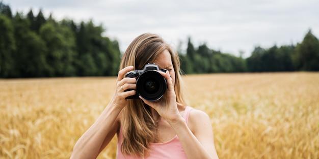 Junge fotografin, die ein foto in richtung der kamera macht, die fokus auf ihrem objektiv anordnet.