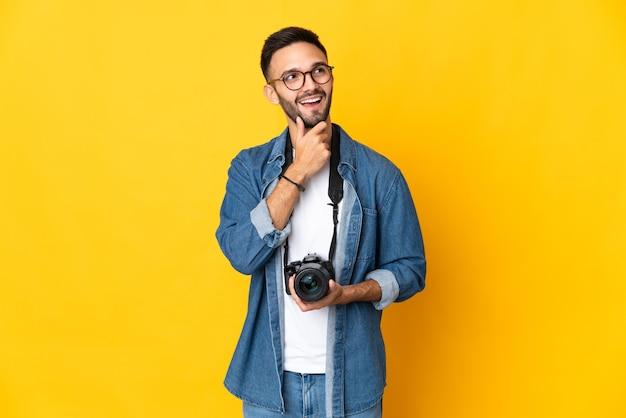 Junge fotografin isoliert auf gelbem hintergrund, die lächelnd nach oben schaut