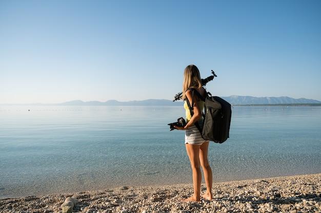Junge fotografin mit stativ auf der schulter am strand
