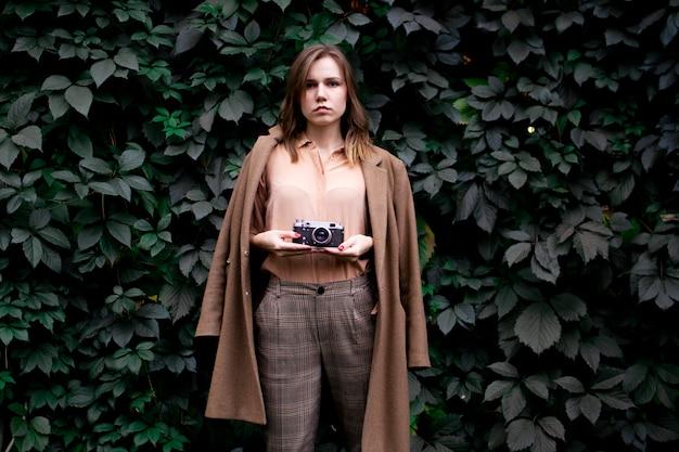 Junge fotografin steht mit einer filmkamera in der nähe einer wand aus blättern im wald, eine frau fotografiert in der natur