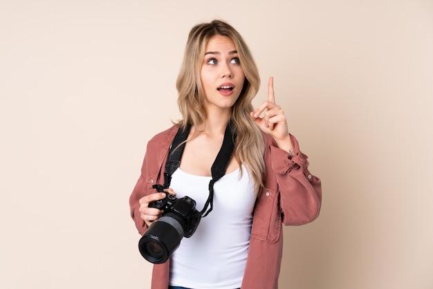 Junge fotografin über isolierte wand, die beabsichtigt, die lösung zu realisieren, während sie einen finger anhebt