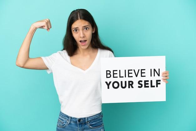 Junge französin isoliert auf blauem hintergrund, die ein plakat mit dem text believe in your self hält und eine starke geste macht