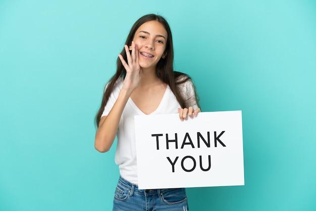 Junge französin isoliert auf blauem hintergrund, die ein plakat mit dem text danke hält und schreit