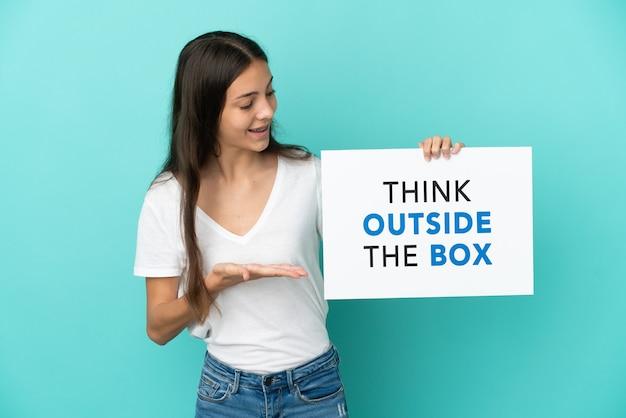Junge französin isoliert auf blauem hintergrund, die ein plakat mit dem text think outside the box hält und darauf zeigt