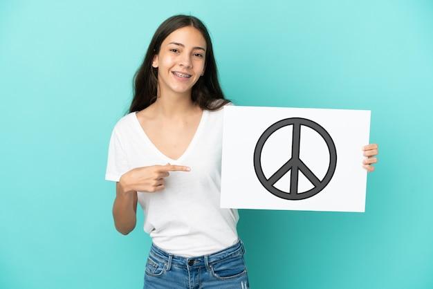 Junge französin isoliert auf blauem hintergrund, die ein plakat mit friedenssymbol hält und darauf zeigt