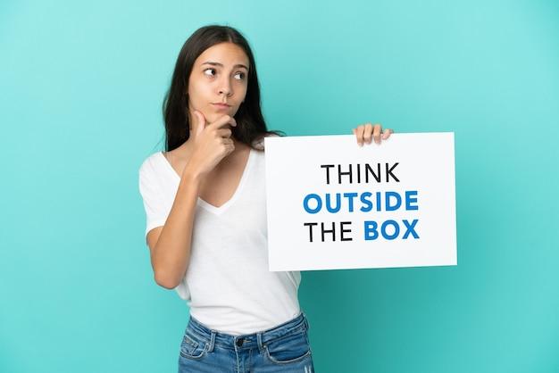 Junge französin isoliert auf blauem hintergrund mit einem plakat mit text think outside the box und thinking