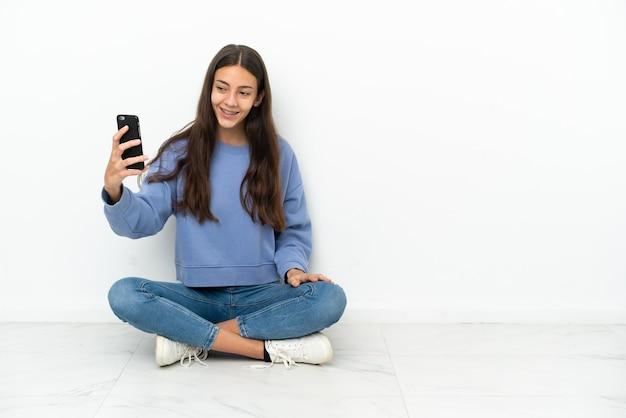 Junge französin sitzt auf dem boden und macht ein selfie