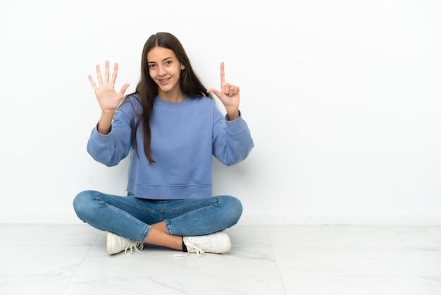 Junge französin sitzt auf dem boden und zählt sieben mit den fingern