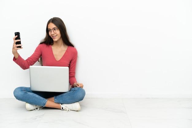 Junge französin sitzt mit ihrem laptop auf dem boden und macht ein selfie