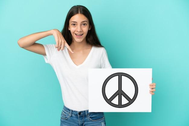 Junge französische frau lokalisiert auf blauem hintergrund, der ein plakat mit friedenssymbol hält und es zeigt