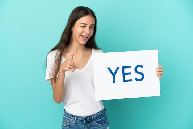 Junge französische frau lokalisiert auf blauem hintergrund, der ein plakat mit text ja hält und nach vorne zeigt