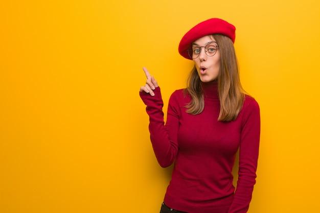 Junge französische künstlerfrau, die auf die seite zeigt