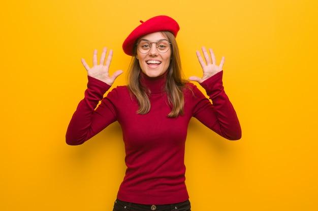 Junge französische künstlerfrau, die nr. zehn zeigt