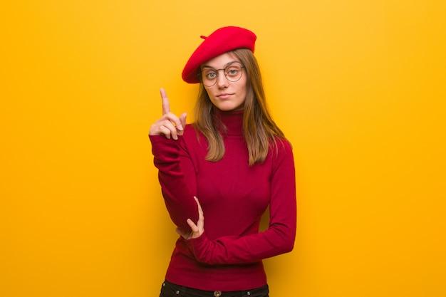 Junge französische künstlerfrau, die nummer eins zeigt