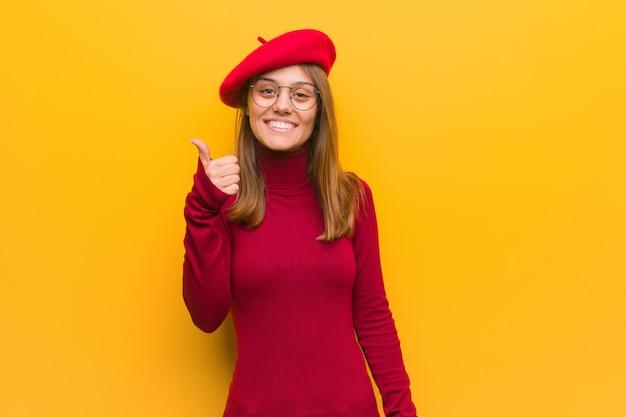 Junge französische künstlerfrau, die oben daumen lächelt und anhebt