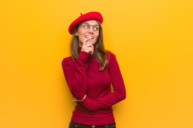 Junge französische künstlerfrau entspannte sich das denken an etwas, das einen kopienraum betrachtet