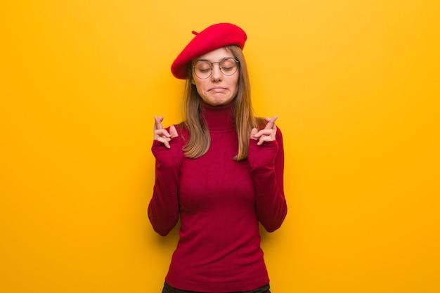 Junge französische künstlerin, die finger für glück kreuzt