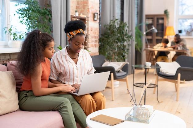 Junge frau afrikanischer abstammung und ihre süße tochter im teenageralter sitzen auf dem sofa im wohnzimmer und surfen im internet oder kaufen zusammen ein