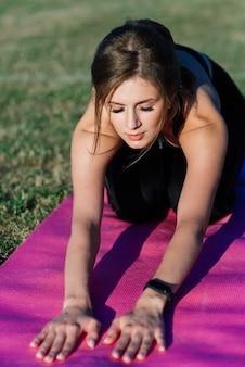 Junge frau allein im stadion beim yoga