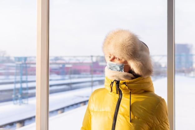Junge frau am bahnhof in einer schutzmaske auf dem gesicht im winterkleidungspassagier