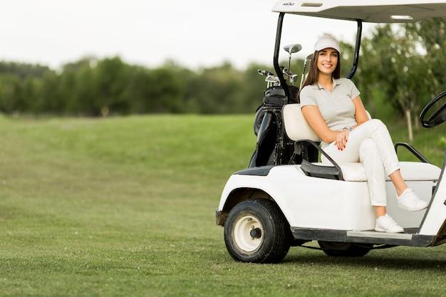 Junge frau am golfwagen