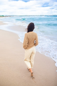Junge frau am strand im sturm