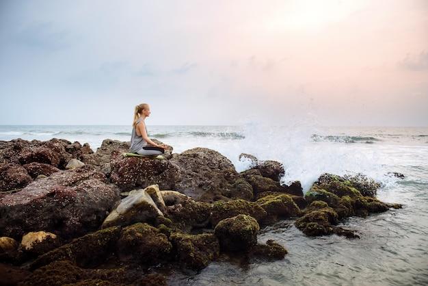 Junge frau am strand praktiziert yoga an der küste während des sonnenuntergangs