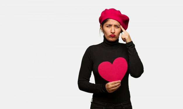 Junge frau am valentinsgrußtag, der eine konzentrationsgeste tut