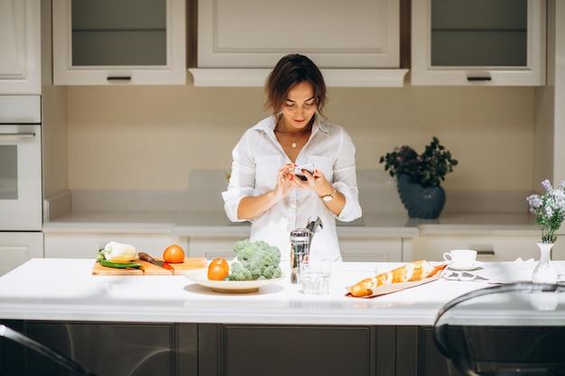 Junge frau an der küche frühstück kochend und am telefon sprechend