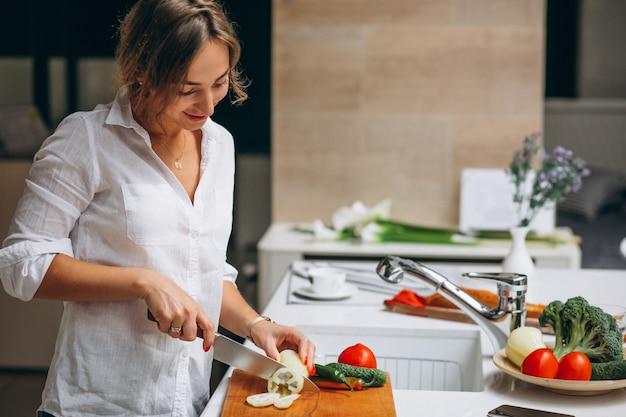 Junge frau an der küche frühstück kochend