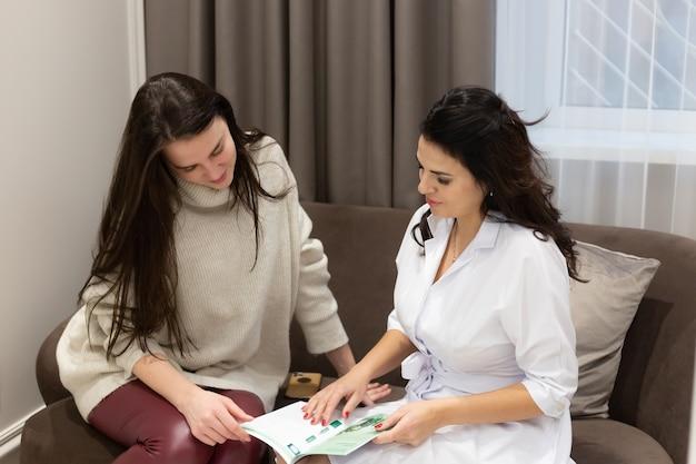 Junge frau an der rezeption beim kosmetiker arzt, zwei frauen sitzen auf dem sofa im salon und kommunizieren, wählen ein verfahren