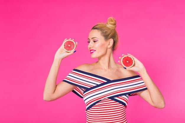 Junge frau an einer rosa wand hält eine geschnittene orange in ihren händen und lacht.