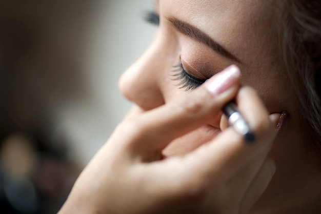 Junge frau angewendet eyeliner.