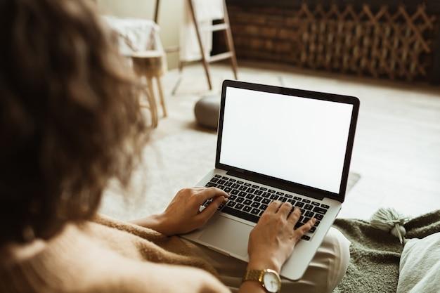 Junge frau arbeiten am laptop mit leerem anzeigebildschirm mit kopierraum. modernes innendesign des wohnzimmers