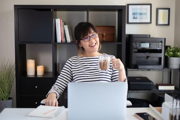 Junge frau arbeiten zu hause büro. lächeln und kaffee trinken.