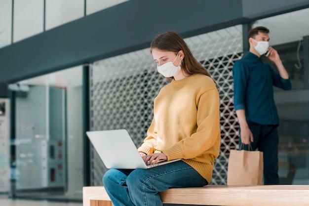 Junge frau arbeitet an einem laptop, während sie vor einem stadtgebäude sitzt. pandemie in der stadt