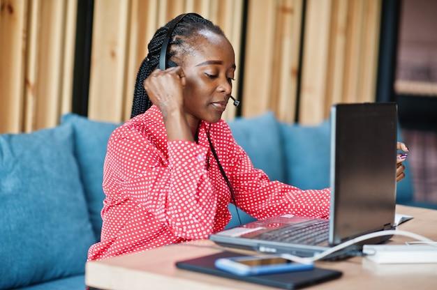 Junge frau arbeitet in einem callcenter-betreiber und kundendienstmitarbeiter, der mikrofon-headsets trägt, die am laptop arbeiten working