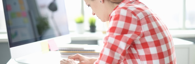 Junge frau arbeitet mit krummem rücken am computer