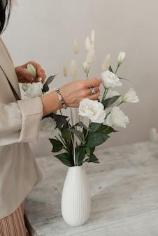 Junge frau arrangiert einen esstisch mit blumen. weiße blumen in einer vase.