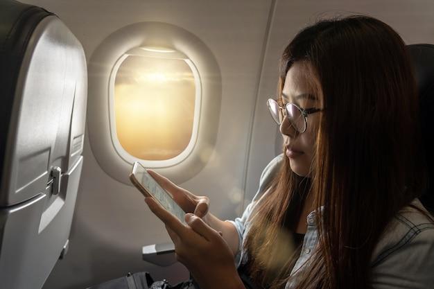 Junge frau asiens, die den intelligenten handy beim reisen innerhalb des flugzeuges verwendet