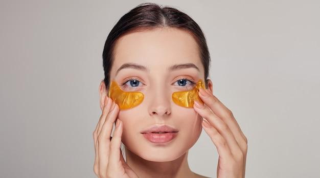 Junge frau auf dem anwenden von goldenen kollagenflecken unter den augen. maske zum entfernen von falten und augenringen.
