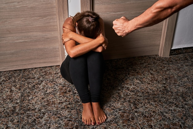 Junge frau auf dem boden, während sie von ihrem partner missbraucht wird. konzept von misshandlung, gewalt und missbrauch gegen frauen
