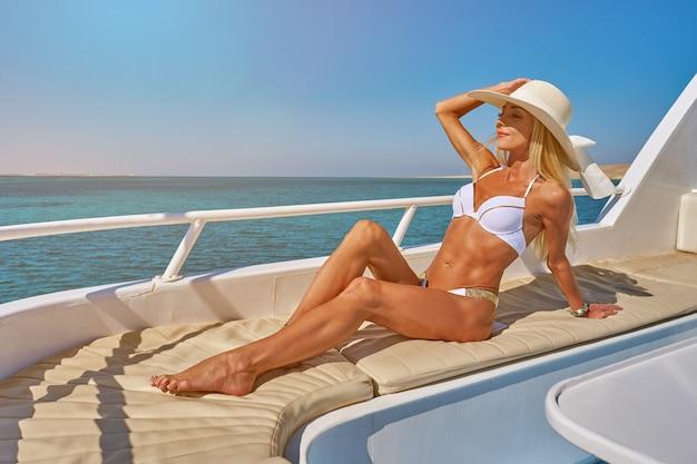 Junge frau auf dem deck eines bootes im offenen meer am sonnigen sommertag