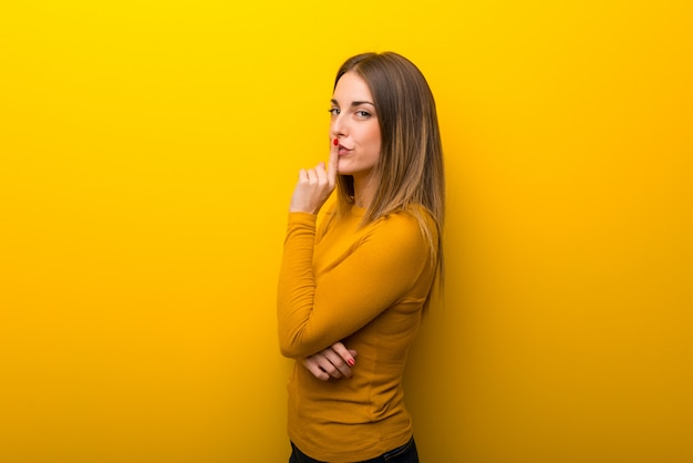 Junge frau auf dem gelben hintergrund, der ein zeichen des schließens der mund- und ruhegeste zeigt