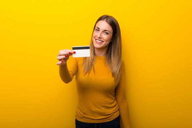 Junge frau auf dem gelben hintergrund, der eine kreditkarte hält