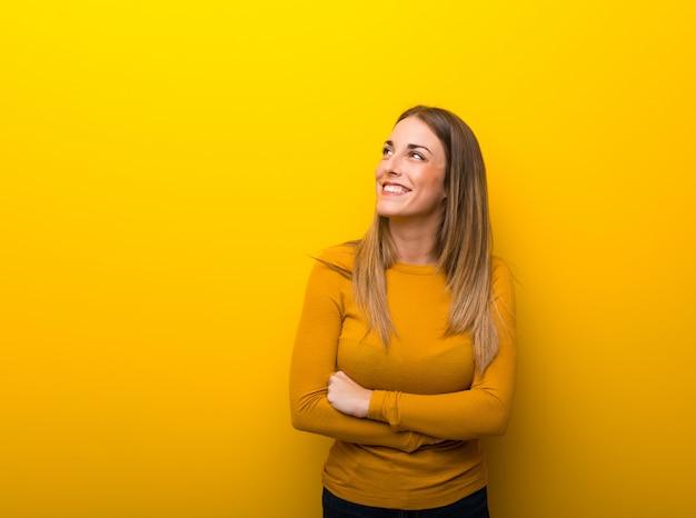 Junge frau auf dem gelben hintergrund, der oben beim lächeln schaut