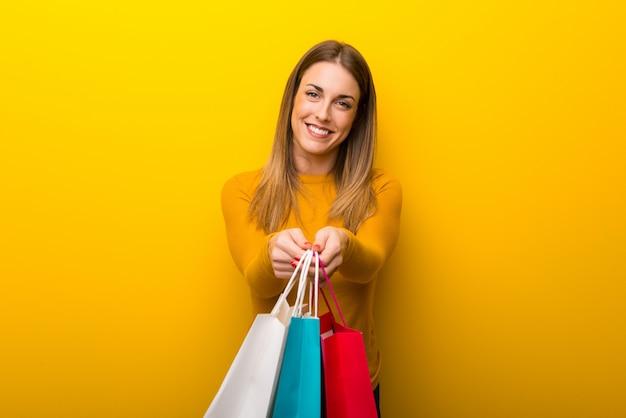 Junge frau auf dem gelben hintergrund, der viele einkaufstaschen hält