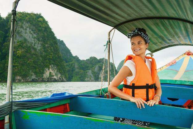 Junge frau auf dem long-tail-boot während ihrer ferien in thailand