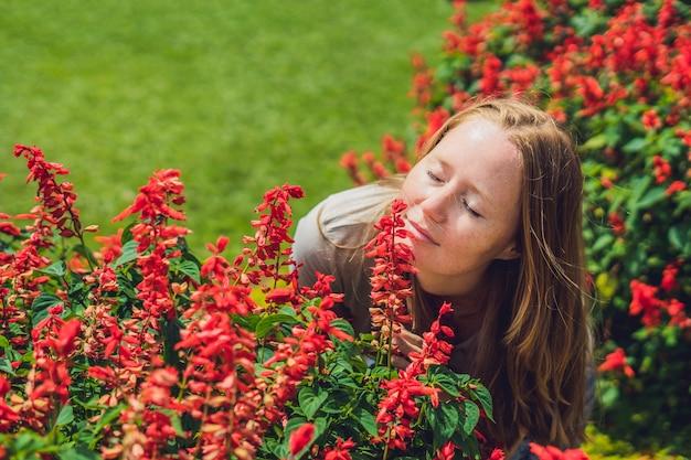 Junge frau auf der oberfläche der hellen rosa hortensienblumen, die im garten blühen